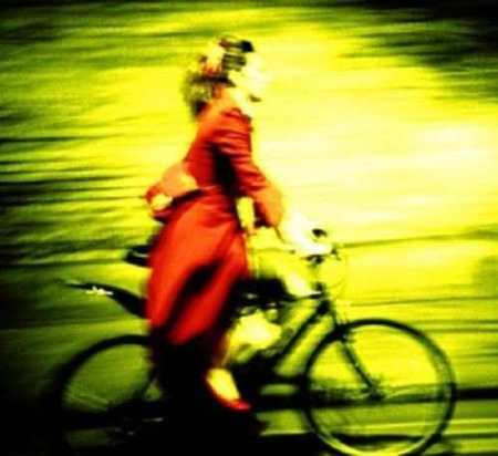 Photo taken by Kevin Meredith of Imogen Heap wearing a long, red coat, riding a bicycle