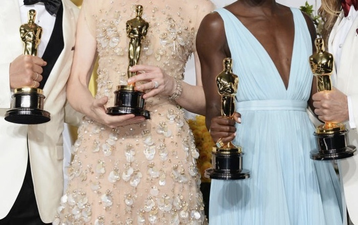 Two women and two men holding Oscar statuettes