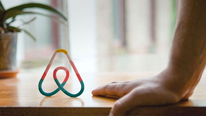 A colorful sculpture of the Airbnb logo standing on a wooden desk