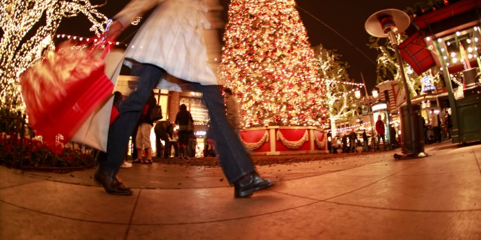 Woman holding holding bags walking past a Christmas tree in a shopping center